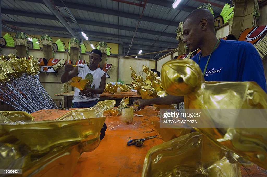 Members of Imperatriz Leopoldinense samba school work on decoration objects during preparations for the famous carnival parade at the Sambodromo, on February 4, 2013 in Rio de Janeiro. The samba schools parade will be held next February 10 and 11. AFP PHOTO/ANTONIO SCORZA