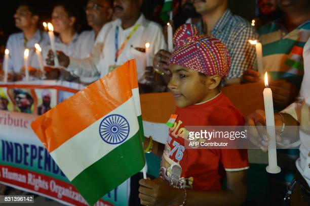 Members of India's Akhil Bhartiya Human Rights Organisation hold lighted candles as they pay tribute to Indian freedom fighters at the India Pakistan...