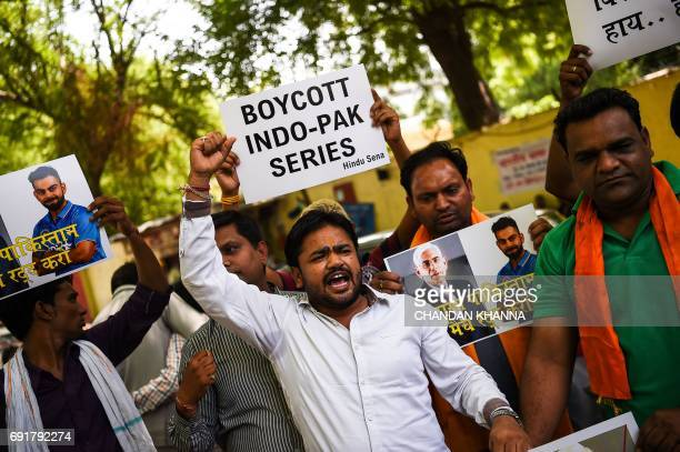 Members of India's rightwing Hindu Sena group carry posters bearing the images of Indian cricket team captain Virat Kohli and president of the Board...