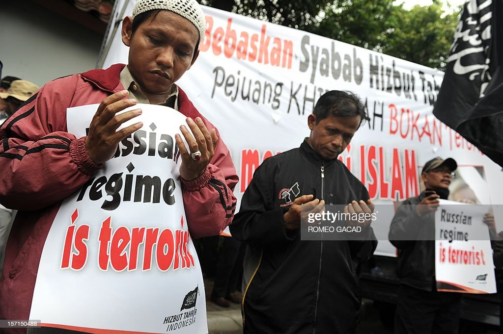 Members of Indonesia's Islamist group Hizb ut-Tahrir pray with placards stating 'Russian regime is terrorist' during a protest outside the Russian embassy in Jakarta on November 29, 2012. Around 200 Indonesians from the Islamist group Hizb ut-Tahrir rallied outside the embassy, demanding the release of six of its leaders and accusing Moscow of planting weapons to smear them.