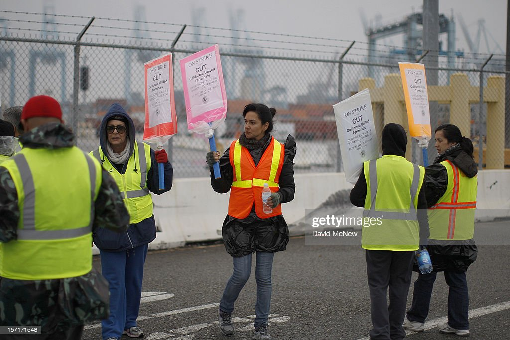 Members of International Longshore and Warehouse Union Local 63 Office Clerical Unit walk a picket line near APM Terminals, halting cargo at the busiest seaport complex in the nation on November 29, 2012 in Long Beach, California. The strike is the largest work stoppage at the ports of Los Angeles and Long Beach since a lockout by shipping companies in 2002, which prompted President George W. Bush to intervene with a court injunction to resolve the standoff.