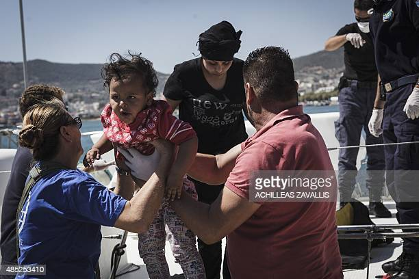 Members of International Organization for Migration help an Iraqi child disembark from a Greek Coast Guard boat that rescued 48 refugees and migrants...