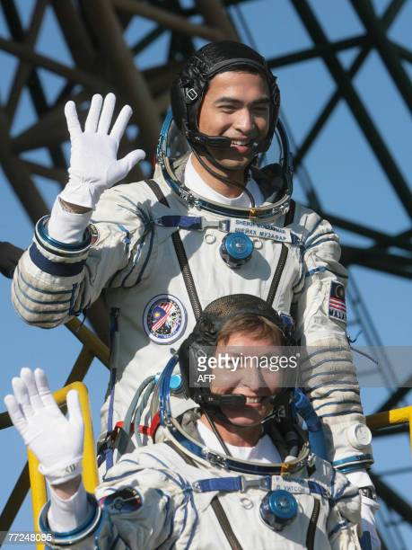 Members of International space crew Sheikh Muszaphar Shukor of Malaysia and US Peggy Whitson wave just before boarding at the Baikonur cosmodrome in...