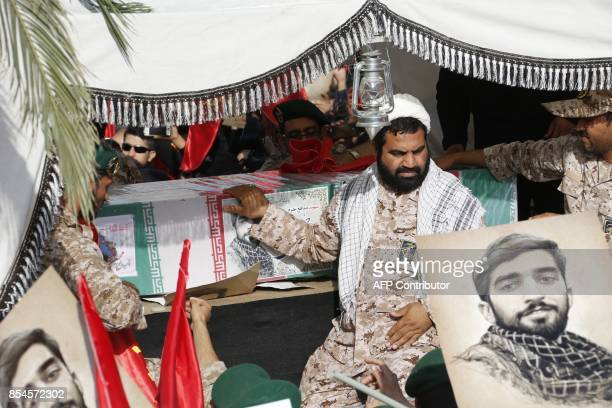 Members of Iran's elite revolutionary guards Corps hold on to the casket of Mohsen Hojaji a young member of the corps who was beheaded in Syria by...