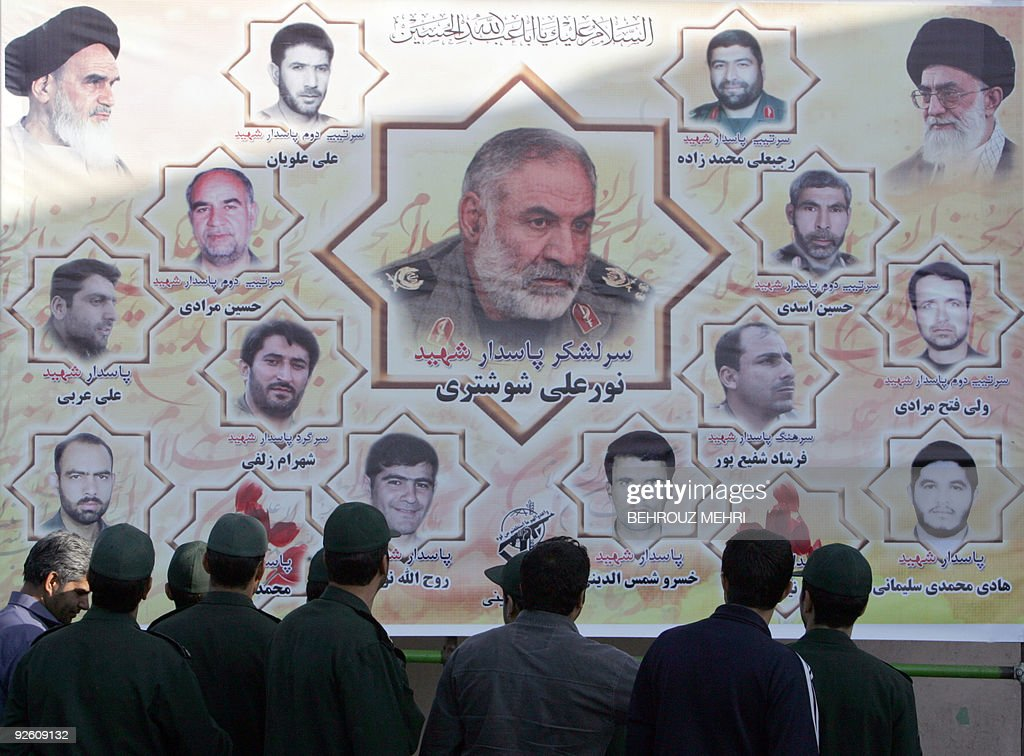 Members of Iran's Revolutionary Guard look at memorial pictures of their commanders and colleagues who were killed in a suicide attack in...