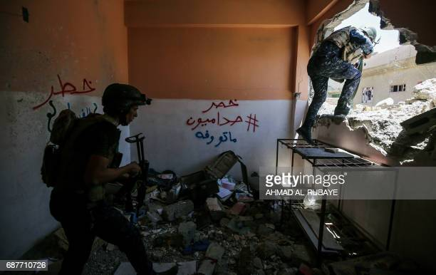 TOPSHOT Members of Iraqi forces climb out of a house on the frontline in the old city of Mosul on May 24 during the ongoing offensive to retake the...
