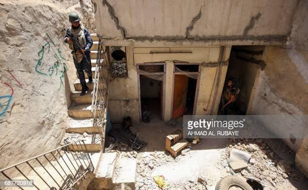 TOPSHOT Members of Iraqi forces walk down stairs in a house on the front line in the old city of Mosul on May 24 during the ongoing offensive to...