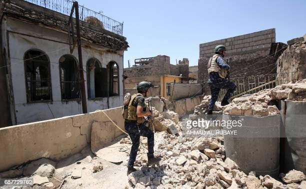TOPSHOT Members of Iraqi forces walk on the roof of a house on the frontline in the old city of Mosul on May 24 during the ongoing offensive to...