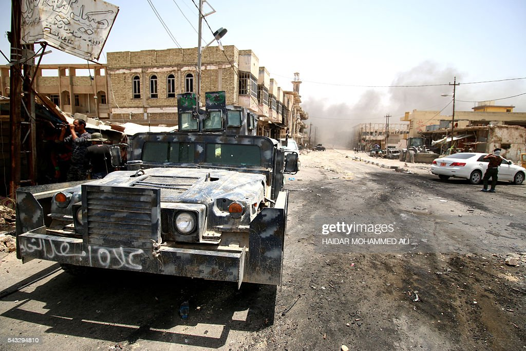 Members of Iraqi government forces patrol a street on June 27, 2016 in western Fallujah, 50 kilometres (30 miles) from the Iraqi capital Baghdad, after Iraqi forces retook the embattled city from the Islamic State group. Iraqi forces took the Islamic State group's last positions in the city of Fallujah on June 26, 2016, establishing full control over one of the jihadists' most emblematic bastions after a month-long operation. ALI
