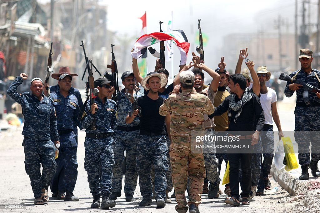 Members of Iraqi police forces celebrate on a street on June 27, 2016 in western Fallujah, 50 kilometres (30 miles) from the Iraqi capital Baghdad, after Iraqi forces retook the embattled city from the Islamic State group. Iraqi forces took the Islamic State group's last positions in the city of Fallujah on June 26, 2016, establishing full control over one of the jihadists' most emblematic bastions after a month-long operation. ALI