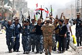 Members of Iraqi police forces celebrate on a street on June 27 2016 in western Fallujah 50 kilometres from the Iraqi capital Baghdad after Iraqi...