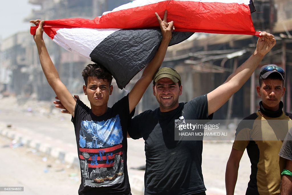 Members of Iraqi police forces celebrate with a national flag on June 27, 2016 in western Fallujah, 50 kilometres (30 miles) from the Iraqi capital Baghdad, after Iraqi forces retook the embattled city from the Islamic State group. Iraqi forces took the Islamic State group's last positions in the city of Fallujah on June 26, 2016, establishing full control over one of the jihadists' most emblematic bastions after a month-long operation. ALI