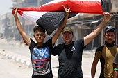Members of Iraqi police forces celebrate with a national flag on June 27 2016 in western Fallujah 50 kilometres from the Iraqi capital Baghdad after...