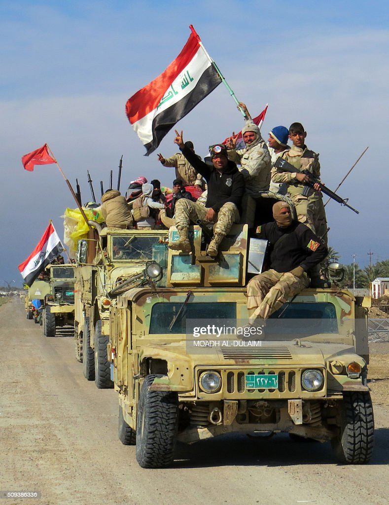 Members of Iraqi pro-governement forces flash the sign of victory and hold national flags atop their vehicle in the Saida area in the southern outskirts of Ramadi, on February 10, 2016, after they retook the region from Islamic State (IS) group jihadists. / AFP / MOADH AL-DULAIMI