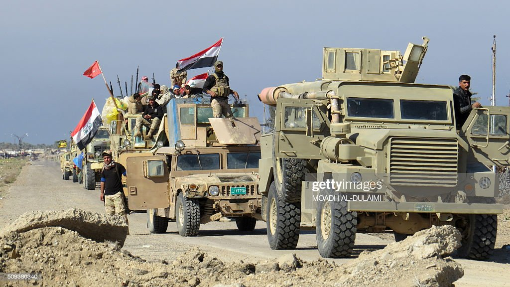 Members of Iraqi pro-governement forces hold national flags atop their vehicle in the Saida area in the southern outskirts of Ramadi, on February 10, 2016, after they retook the region from Islamic State (IS) group jihadists. / AFP / MOADH AL-DULAIMI
