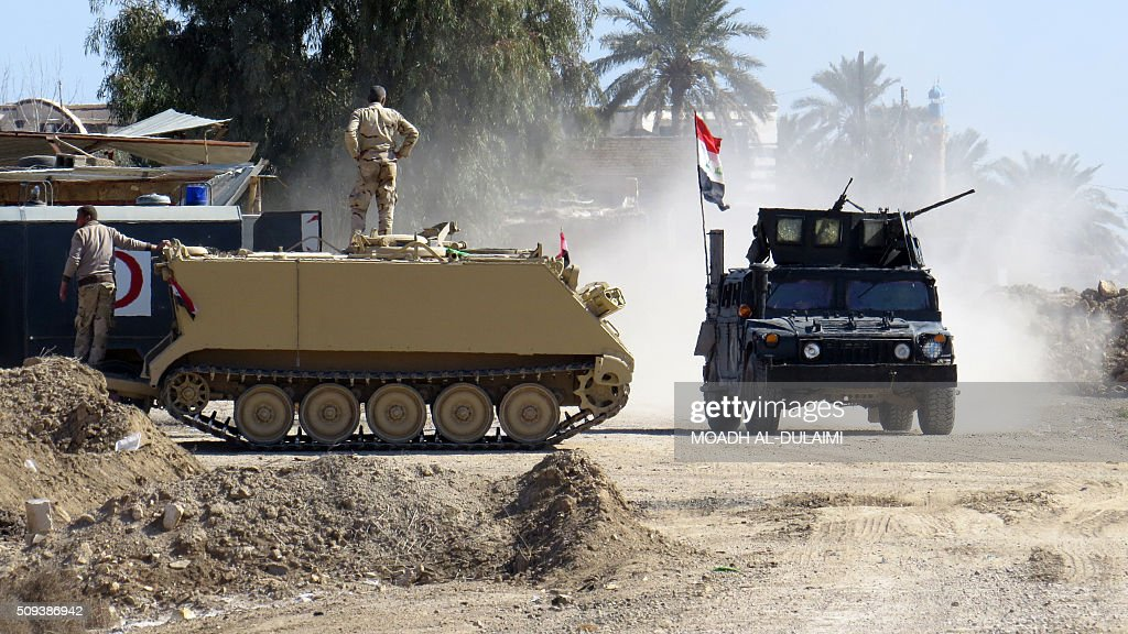 Members of Iraqi pro-governement forces stand next to their vehicles in the Saida area in the southern outskirts of Ramadi, on February 10, 2016, after they retook the region from Islamic State (IS) group jihadists. / AFP / MOADH AL-DULAIMI