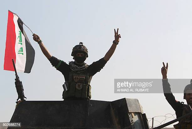 Members of Iraq's elite counterterrorism service flash the 'V' for victory sign on December 28 2015 at the heavily damaged government complex after...