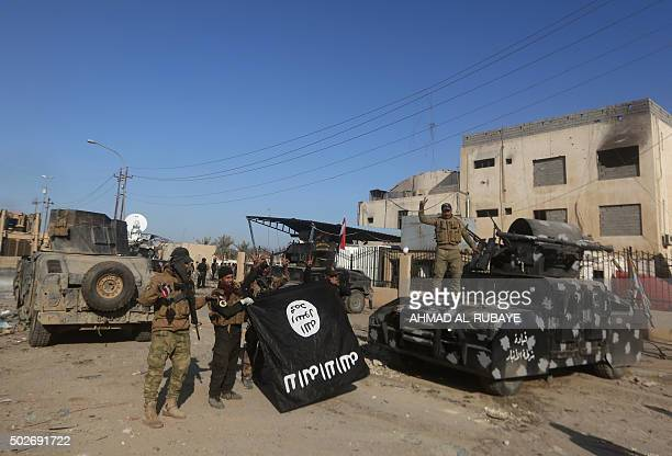 Members of Iraq's elite counterterrorism service hold the Islamic State group's flag and flash the 'V' for victory sign on December 28 2015 after...