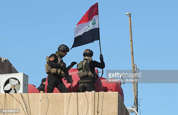 Members of Iraq's elite counterterrorism service place their national flag on December 28 2015 on the roof of a building at the government complex...