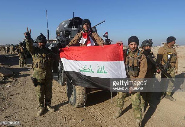 Members of Iraq's elite counterterrorism service pose with their national flag on December 29 2015 in the city of Ramadi the capital of Iraq's Anbar...