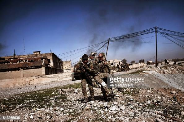 TOPSHOT Members of Iraq's elite Rapid Response Division carry a wounded comrade in the northern city of Mosul as Iraqi forces continue the offensive...