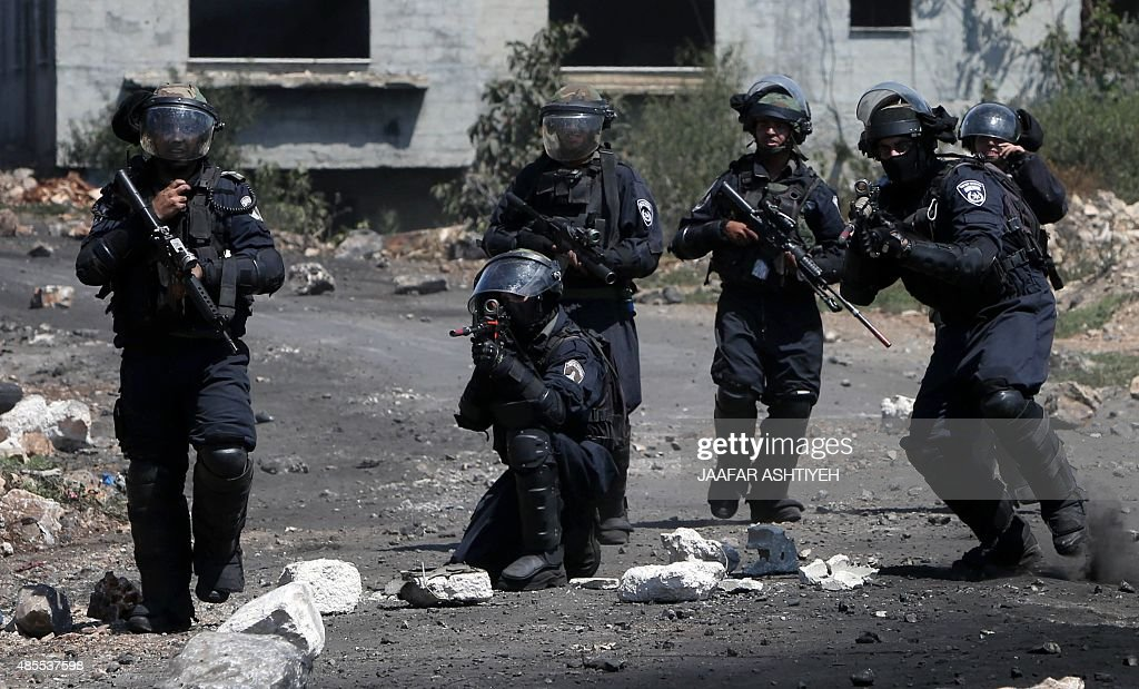 Members of Israeli security forces aims their weapons towards Palestinian stone throwers during clashes following a demonstration against the...
