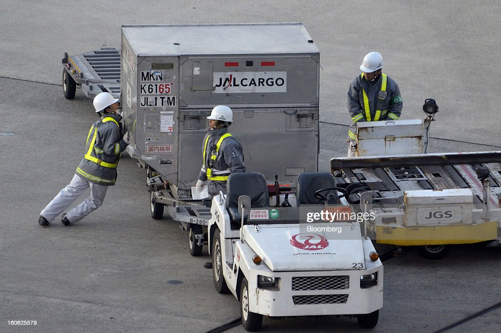 Members of Japan Airlines Co.'s ground staff prepare cargo containers for loading onto an aircraft at Haneda Airport in Tokyo, Japan, on Sunday, Feb. 3, 2013. Japan Airlines, the nation's largest carrier by market value, is scheduled to release earnings on Feb. 4. Photographer: Akio Kon/Bloomberg via Getty Images