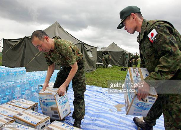 Members of Japanese Ground SelfDefense Forces medical team move boxes of Japanese natural water as part setting up their base camp in an area of...