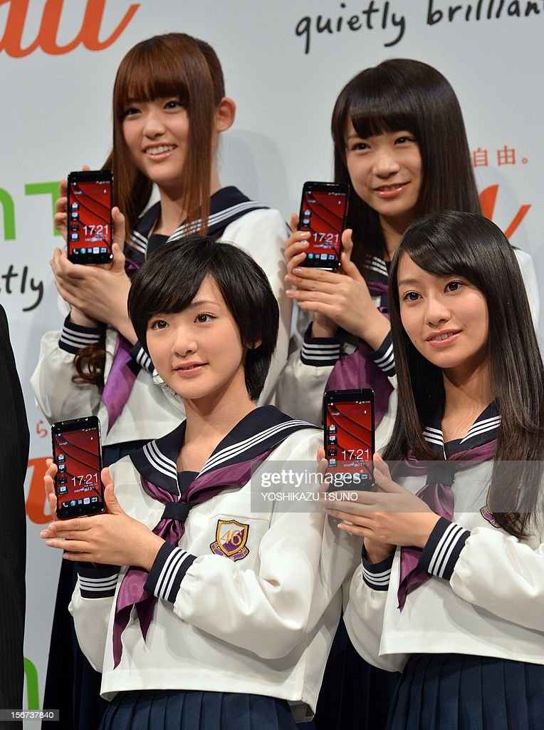 Members of Japanese pop group 'Nogizaka 46' display Taiwan's electronics giant HTC's new smartphone 'HTCJ butterfly' for Japanese mobile carrier KDDI in Tokyo on November 20, 2012. The new smartphone has a quad-core CPU, 5-inch sized high-definition LCD display and an 8 mega-pixel CMOS camera on its slim body. AFP PHOTO / Yoshikazu TSUNO