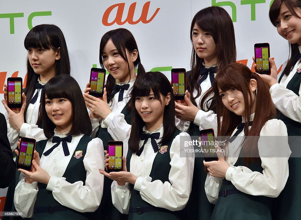 Members of Japanese pop group Nogizaka 46 display the new smart phone of Taiwanese electronics maker HTC 'HTC J butterfly HTL23' at the launch event in Tokyo on August 19, 2014. The new HTC butterfly will go on sale through KDDI shops in Japan from August 29. AFP PHOTO / Yoshikazu TSUNO