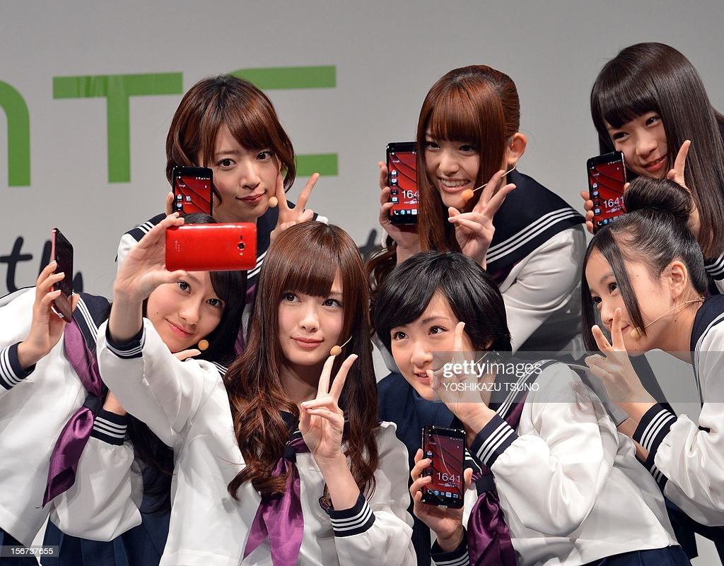 Members of Japanese pop group 'Nogizaka 46' take their self portraits as they display Taiwan's electronics giant HTC's new smartphone 'HTCJ butterfly' for Japanese mobile carrier KDDI in Tokyo on November 20, 2012. The new smartphone has a quad-core CPU, 5-inch sized high-definition LCD display and an 8 mega-pixel CMOS camera on its slim body. AFP PHOTO / Yoshikazu TSUNO