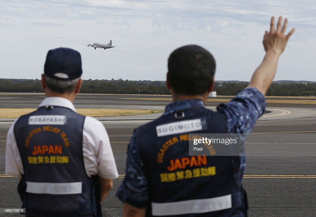 Members of Japan's disaster relief team wave off a Japan Maritime SelfDefence Force Lockheed P3C Orion aircraft as it takes off from the RAAF base...