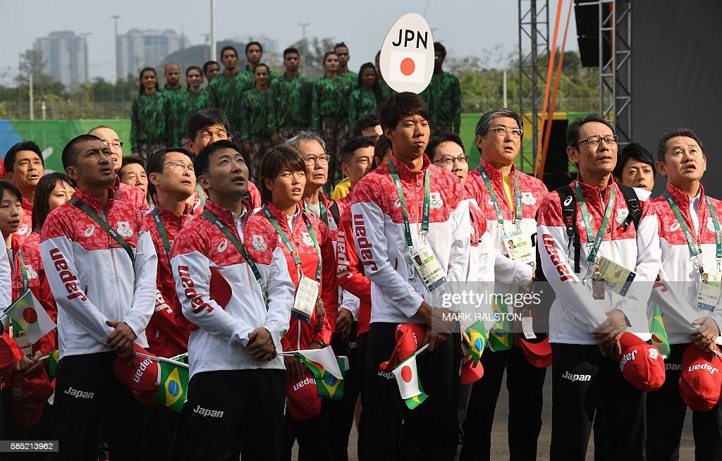 Members of Japan's Olympic team sing the national anthem as they attend a welcoming ceremony at the athletes village of the Rio 2016 Olympic Games in...