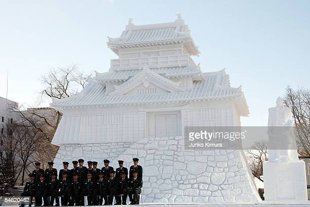 Members of Japan's Self Defence Force gather in front of a snow castle ahead of the opening of the 60th Sapporo Snow Festival at Odori Park on...
