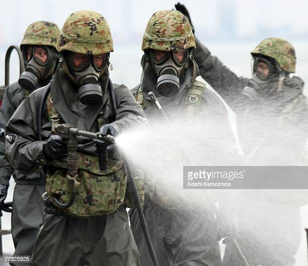 Members of Japan's SelfDefence Force exercise the removal of unidentified chemical substances with an antichemical suit during the Proliferation...
