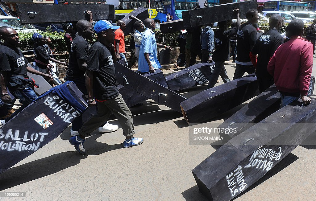 Members of Kenya's civil activists pull mock coffins as thet take to the streets on the capital Nairobi during a January 16, 2013 'State Burial' for the members of the Kenyan parliament propasal to award themselves millions of shillings in a selfish send-off deal that included state funerals. Kenya's president rejected plans by members of parliament to triple their end-of-term bonuses and award themselves diplomatic passports, bodyguards for life and state funerals. In their last act before parliament closed for March 4 elections, Kenyan lawmakers, already among the best paid in the world, tried for a second time in a few months to increase their end-term bonus to 9.3 million shillings ($107,200) each.