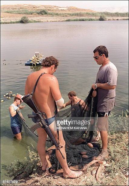 Members of kibbutz Kfar Ruppin located along the IsraeliJordanian border work the fish ponds 07 September 1989 armed with an USmade M16 machine gun...