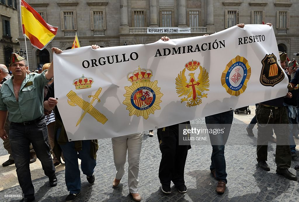 Members of 'La Hermandad de Caballeros Legionarios de Barcelona' (Brotherhood of the Knights Legion of Barcelona) hold a banner reading, 'pride admiration respect' during a demonstration in support of the Spanish army on May 28, 2016 in Barcelona. / AFP / LLUIS