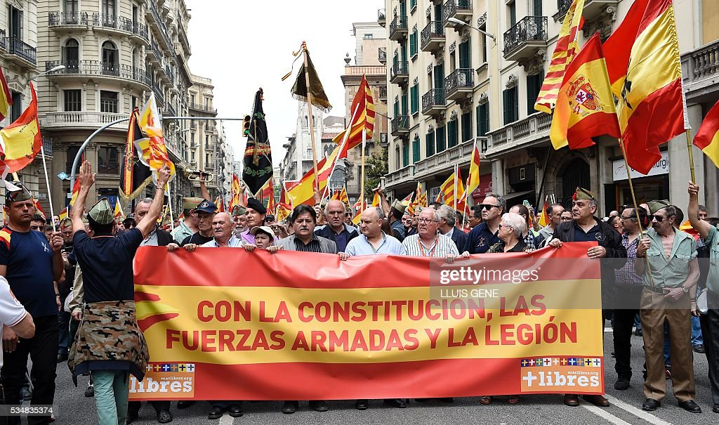 Members of 'La Hermandad de Caballeros Legionarios de Barcelona' (Brotherhood of the Knights Legion of Barcelona) hold a banner reading, 'The Armed Forces and the Legion are with the Spanish Constitution' during a demonstration in support of the Spanish army on May 28, 2016 in Barcelona. / AFP / LLUIS