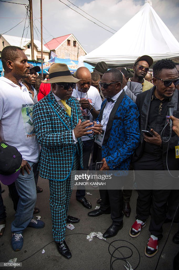Members of La SAPE movement ('Societe des Ambianceurs et des Personnes Elegantes' or 'Society of Ambiance-Makers and Elegant People') gather with others in the streets of 'Village Molokoi', in the Matonge neighborhood of Kinshasa, to pay tribute to late rumba musician Papa Wemba on May 2, 2016. Democratic Republic of Congo's rumba king Papa Wemba was posthumously awarded one of his country's highest honours, a week after he collapsed on stage and died aged 66. / AFP / JUNIOR