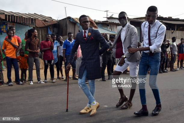 Members of La SAPE movement pose as they parade in a street of Abidjan on April 24 2017 during a day of tribute to late Congolese rumba star Papa...