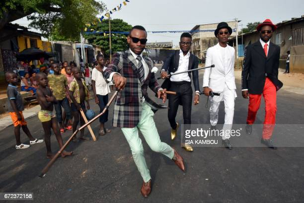 Members of La SAPE movement parade in a street of Abidjan on April 24 2017 during a day of tribute to late Congolese rumba star Papa Wemba during a...