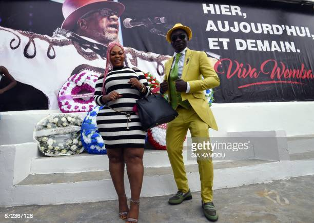 Members of La SAPE movement pose in front of a poster picturing late Congolese rumba star Papa Wemba during a day of tribute on April 24 2017 in...