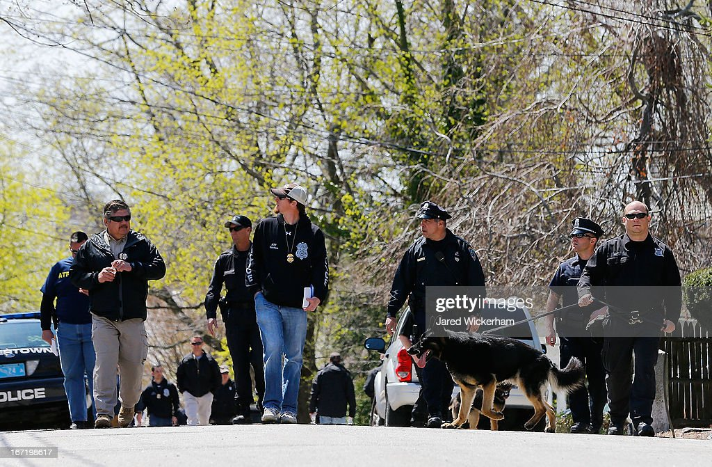 Members of law enforcement, including many K-9 units, investigate the scene while executing a second sweep of the area around Franklin Street on April 22, 2013 in Watertown, Massachusetts. A manhunt ended for Dzhokhar A. Tsarnaev, 19, a suspect in the Boston Marathon bombing after he was apprehended on a boat parked on a residential property in Watertown, Massachusetts. He has been charged with one count of using a weapon of mass destruction and one count of malicious destruction of property by means of an explosive device resulting in death. His brother Tamerlan Tsarnaev, 26, the other suspect, was shot and killed after a car chase and shootout with police. The bombing, on April 15 at the finish line of the marathon, killed three people and wounded at least 170.