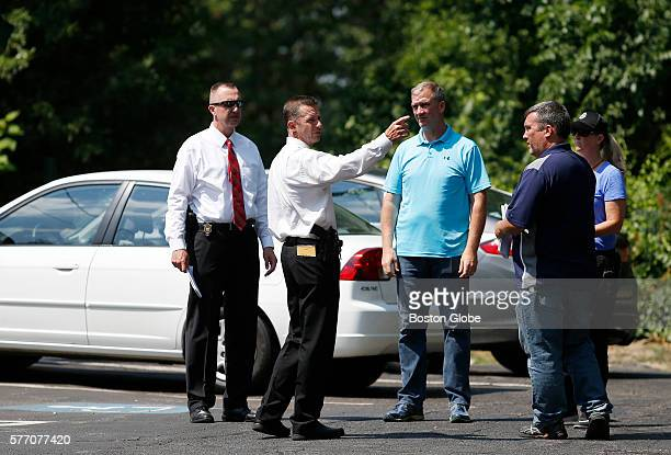 Members of law enforcement talk in the driveway of Sully's Ice Cream after a man who led police on a chase was shot at Sully's Ice Cream in...