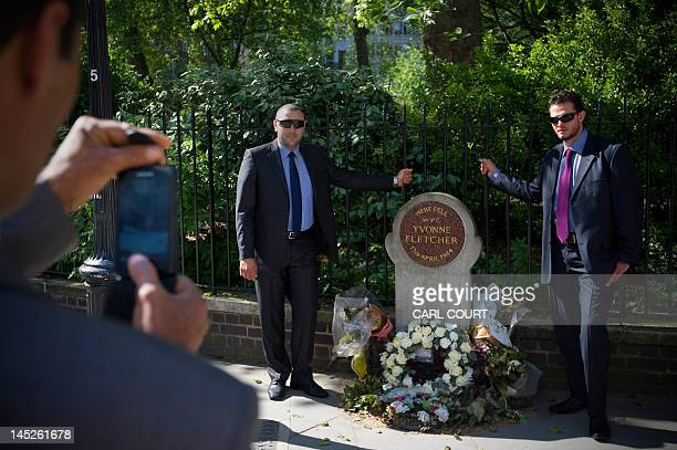 Members of Libyan interim Prime Minister Abdel Rahim alKib's security detail have their pictures taken in London on May 25 beside the memorial to...