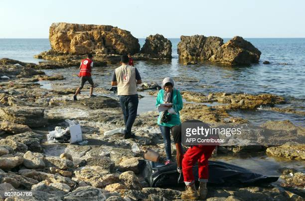 Members of Libya's Red Crescent recover the body of a migrant that washed ashore in Tajura a coastal suburb of the Libyan capital Tripoli on June 28...