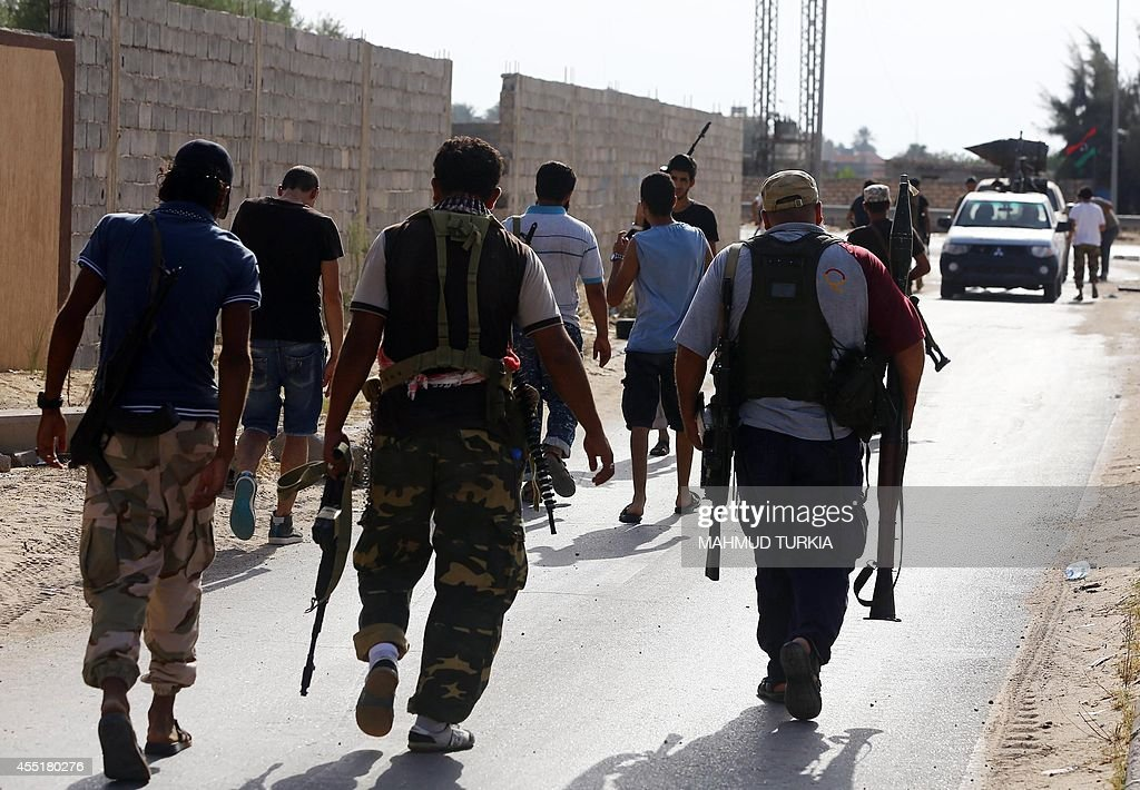 Members of Libya's shield brigade and some local fighters from the western region walk carrying their weapons during clashes with gunmen accused of...