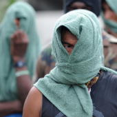 Members of 'Los Rastrojos' bandit group cover their face with towels as they surrender at the Voltigeros Battalion on May 21 2009 in Uraba Antioquia...