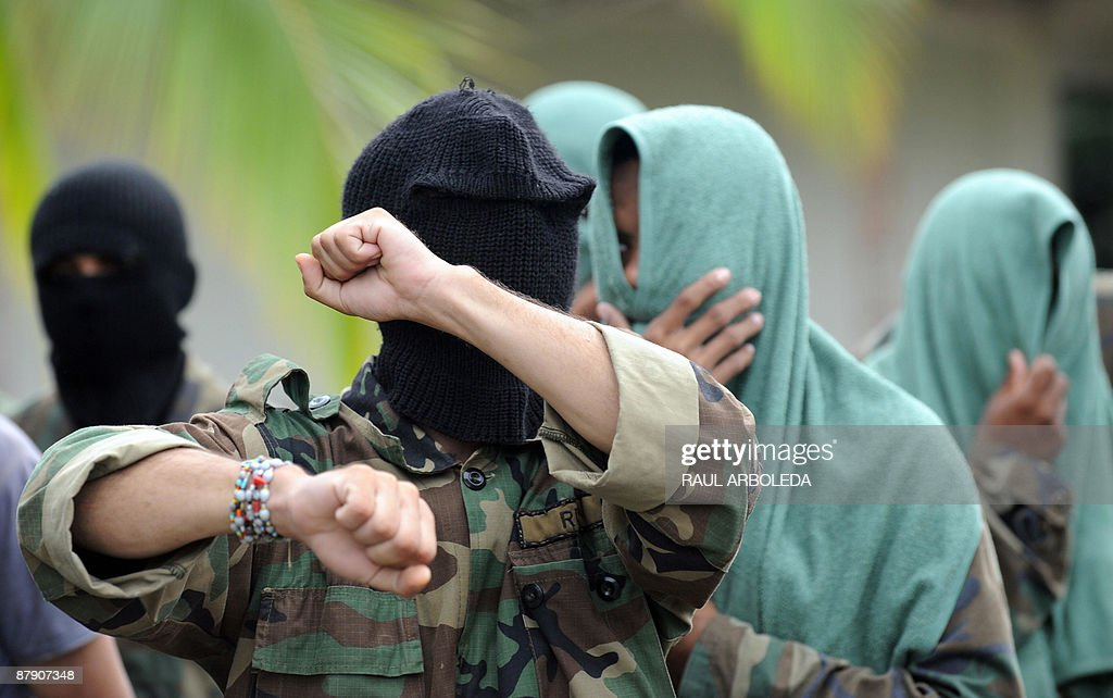 Members of 'Los Rastrojos' bandit group cover their face with towels and balaclavas as they surrender at the Voltigeros Battalion on May 21, 2009 in Uraba, Antioquia department, Colombia. 112 members of 'Los Rastrojos', a group of former AUC paramilitary right-wing guerrillas who became drug traffickers, have surrendered in Nuqui, Choco deparment, in the last days. AFP PHOTO / Raul ARBOLEDA
